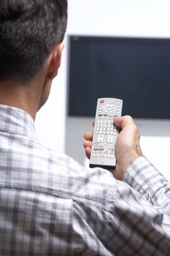 a_man_with_a_remote_control_sitting_in_front_of_a_tv_screen_and_switching_a_channel_or_switching_off
